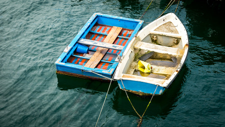 skiff: Curious rectangular and striped boat at the jetty Stock Photo