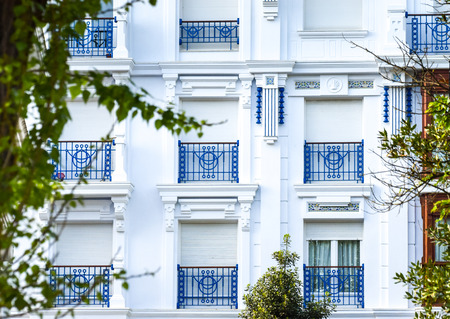 Facade detail with its white windows and blue railings