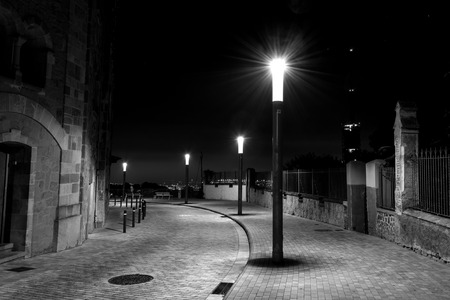 Night photo of row of streetlights in a curved and cobbled Street