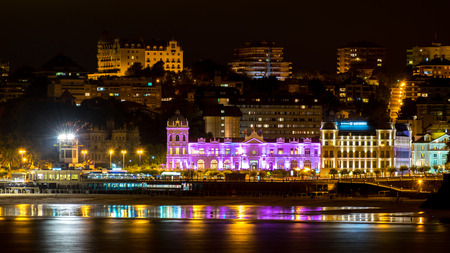 iluminated: SANTANDER, SPAIN - AUGUST 29, 2015: Panoramic view of Great Casino of Santander city iluminated at night and reflections in the water of the beach Cantabria, Spain