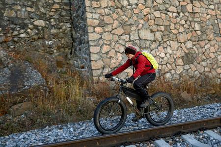 Tourist rides a bike with wide wheels along the shore of Lake Baikal.