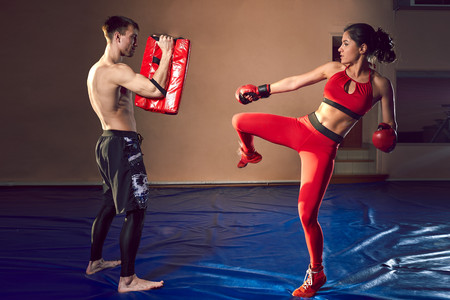 The guy and the girl work out the punches in the gym.
