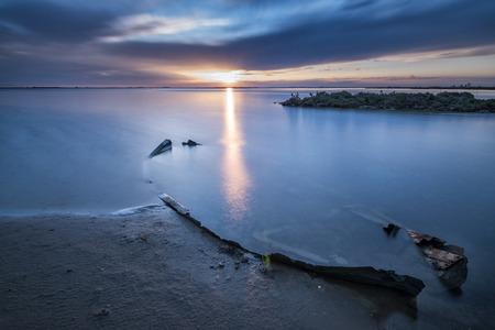 Sunrise at Delta de lEbre, Tarragona, Catalonia, Spain with a sunken boat in the foreground. Stock Photo