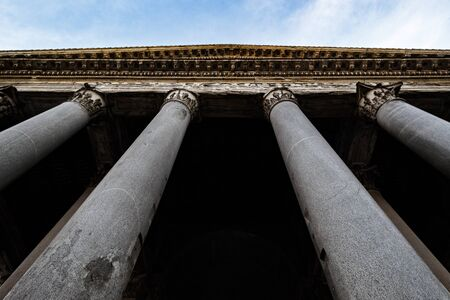 Corinthian columns from the portico of the Pantheon, Rome, Italy, also known as Santa Maria Rotonda. View from below, under a blue sky with clouds. Stock Photo