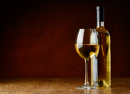 bootle: A glass of white wine and a bootle of white wine oni a wooden table in a a winecellar Stock Photo