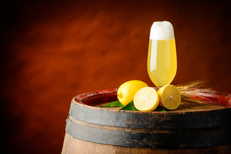 One glass of Radler beer with lemons and wheat on top of a old wooden barrel