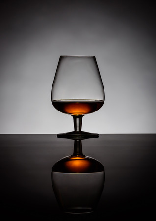 backlit: One glass of cognac backlit and reflection
