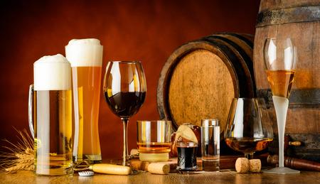 bebidas alcohólicas en la mesa de madera en vasos, tazas y disparos con el barril en el fondo Foto de archivo