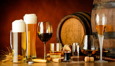 alcoholic drinks on wooden table in glasses, mugs and shots with barrel in background Archivio Fotografico