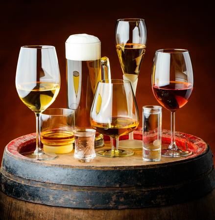 bebidas alcohÓlicas: Alcoholic drinks in glasses on a wooden barrel in a cellar.