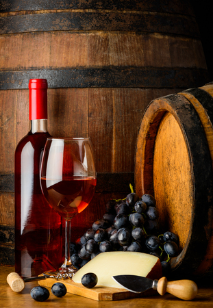 bootle: Rose wine bootle and glass, cheese and grapes in still life on wooden barrel background