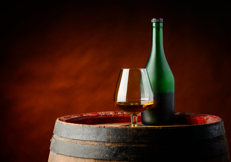 stillife: one glass and bottle of cognac in still-life on a rustic wood barrel in a basement