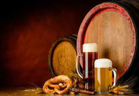 mug of ale: dark and golden beer with barrel, brezel and wheat on dark background