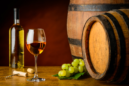 pinot: Still life with one glass and bottle of pinot gris wine in tavern with wooden barrels Stock Photo