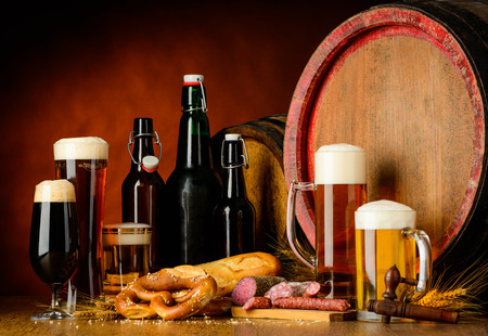 types of glasses: glasses and bottles of beer on rustic background with, barrel, wheat, pretzel and sausagel. Different types of beer, dark, golden blond and bitter. Stock Photo