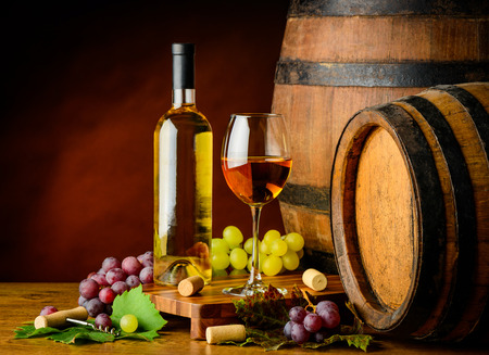 still life of wine: Still life with white wine in cellar on wooden table and barrels