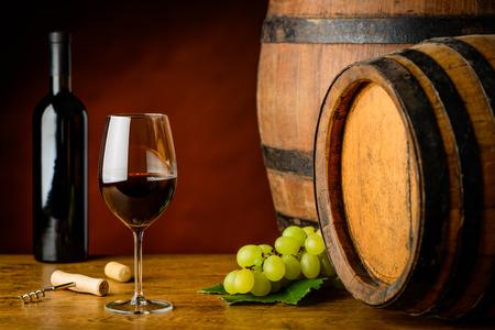sauvignon: Red Cabernet Sauvignon wine in still life with white grapes and wooden barrels