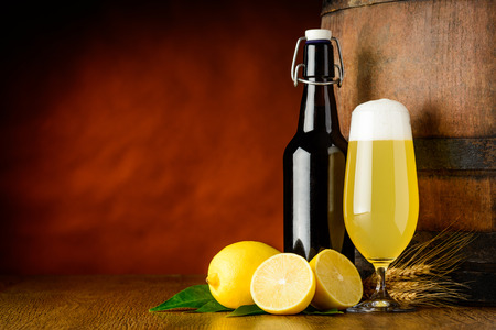 A bottle and a glass of Radler Beer with lemon on wooden table and a wood barrel