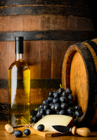 chese: White wine in bottle with dark grapes and chese with wooden background Stock Photo