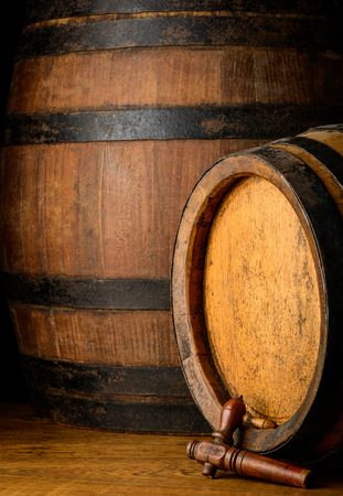 Barrels in a cellar on wooden table. Stock Photo