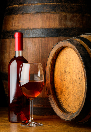 wine glasses: Rose wine in a glass and a bottle on wooden background with barrles