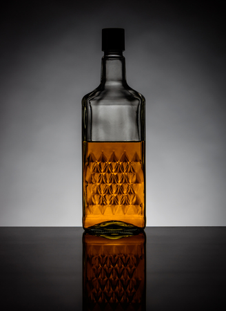 brandy: One bottle of cognac brandy backlit and with reflection Stock Photo