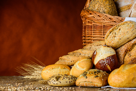stillife: bread basket and bun in traditional still-life on wood table with grain and wheat and flour Stock Photo