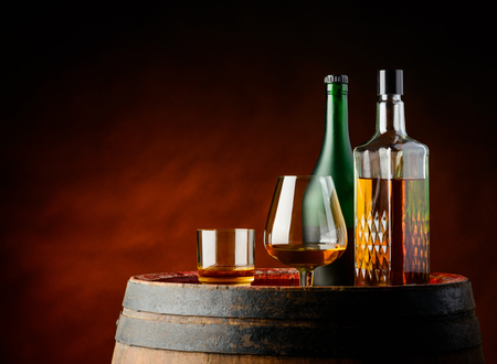 whisky glass: Glass and bottle of cognac and whisky on a wooden barrel Stock Photo