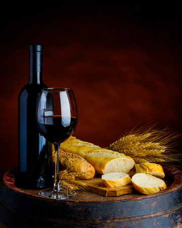 rustical: Glass and bottle of red wine, baguettes and wheat in a rustical setup Stock Photo