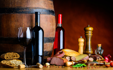 One glass of red wine and two bottles of rose and red wine in a rustic cellar with food.
