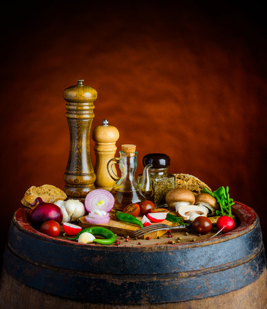 stillife: fresh vegtables, olive-oil on rustic background in still life