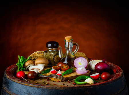 stillife: Vegetarian food on rustic background with onions, tomatoes, garlic, mushrooms, olive-oil in still life