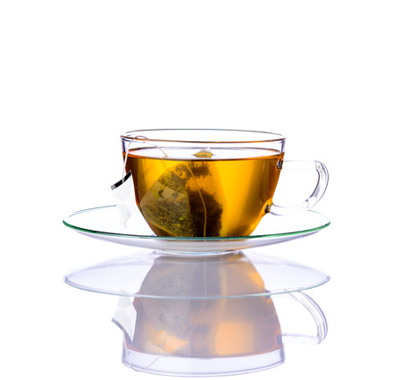 Single glass-cup of Yellow tea and tea-bag isolated on white background