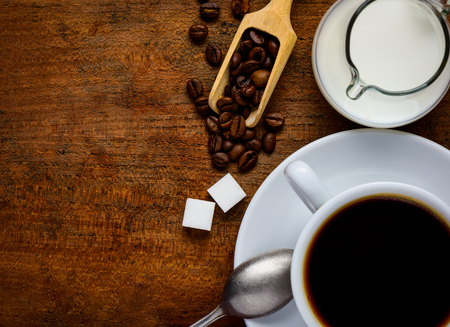 Top view of wooden table-top with Cup of Coffe, Coffee-Beans, sugar and milk with copy-space Stock Photo - 50930645