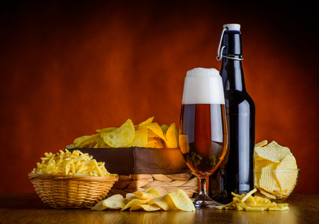 beerglass: Glass and Bottle Beer with junk-food, potato-chips in still life Stock Photo