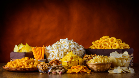 Different types of snacks, chips, nuts and popcorn in still life