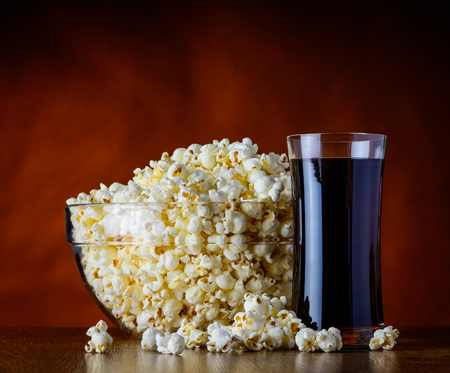 bowl of popcorn: Bowl full with popcorn and a glass of cola on wooden table Stock Photo