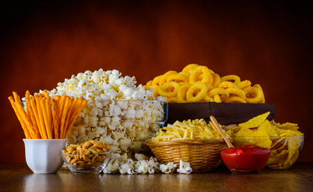differnt: Differnt Types of Junk food, Popcorn, salty-sticks, salty-crackers on wooden table in still-life