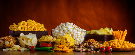 Panoramic still life with salty-snacks, potato-chips, popcorn and dip Stock Photo