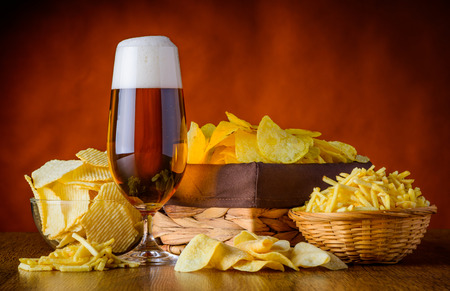 Beer and salty potato-snacks, chips and sticks in still-life