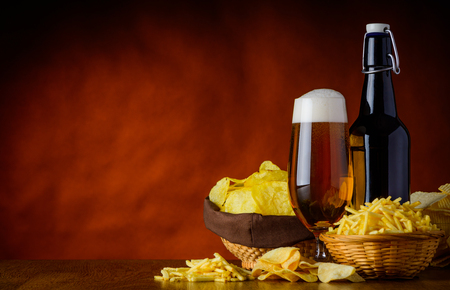 beerglass: Junk-Food salty snacks, potato-chips and beer on wooden table-top with copy-space
