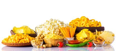 Verschillende soorten Junk food op een witte achtergrond. Potato Chips, pinda's en popcorn