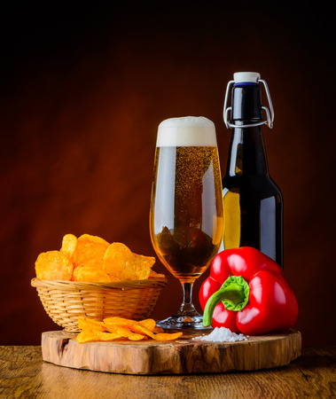 food still: Glass and Bottle Beer with potato chips and red pepper