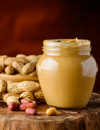 glass jar: Glass Jar of peanut butter and some peanuts in background