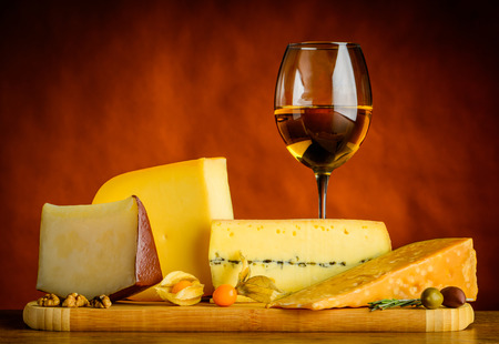 hard cheese: Glass of white wine and gouda cheese and other hard cheese with food