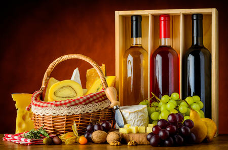 Three bottles of wine with basket cheese, grapes and food in still life Stock Photo