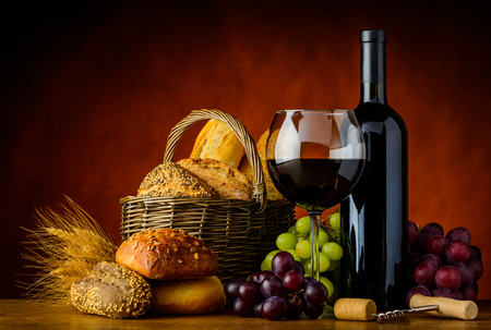 Glass and Bottle red wine with basket of bread in rustic still life