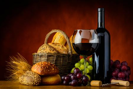pan y vino: Vidrio y botella de vino rojo con la cesta de pan rústico en la naturaleza muerta