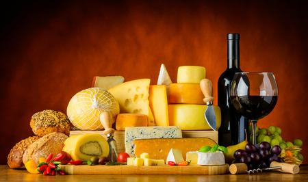 pan y vino: Botella y vidrio de vino tinto con queso, pan y alimentos