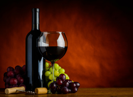 Bottiglia e bicchiere di vino rosso con l'uva nella natura morta con copia-spazio Archivio Fotografico
